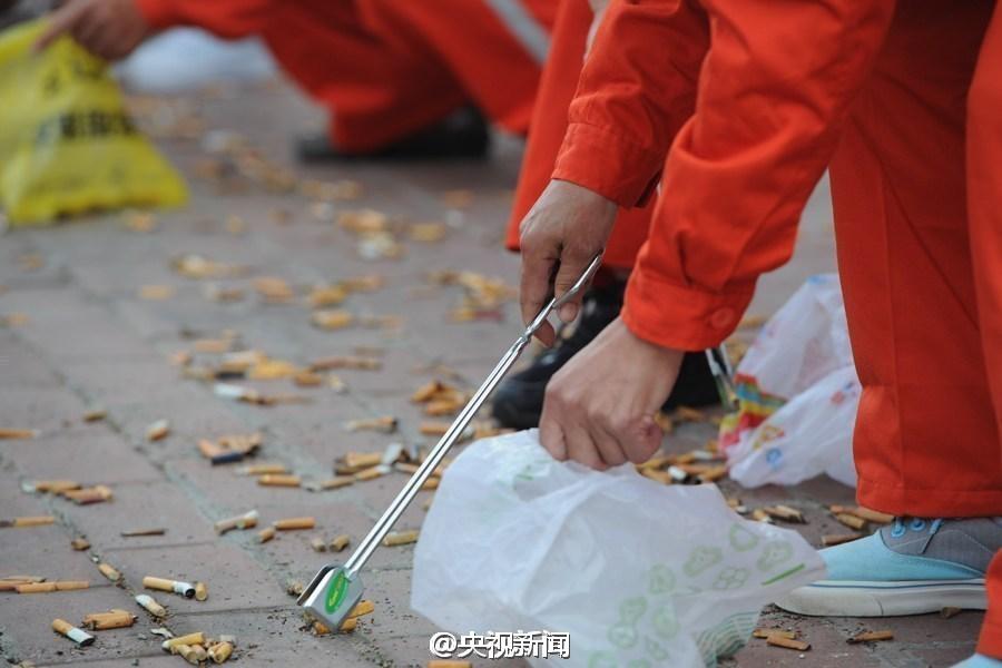 A sanitation worker picks up cigarette butts