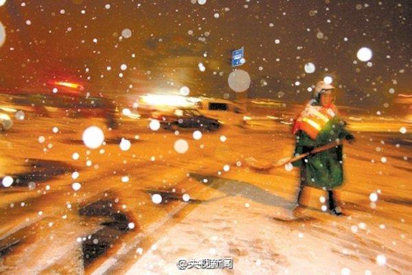 A sanitation worker shovels snow