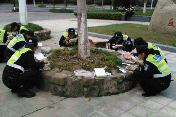 Chinese police officers eating a simple meal in a park.