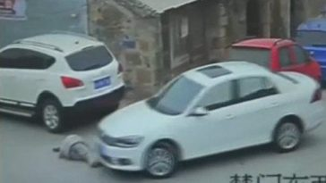 A white car moments before running over a fallen old man in Zhejiang, China.