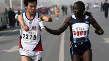One runner helps another disabled without hands drink water in a marathon.