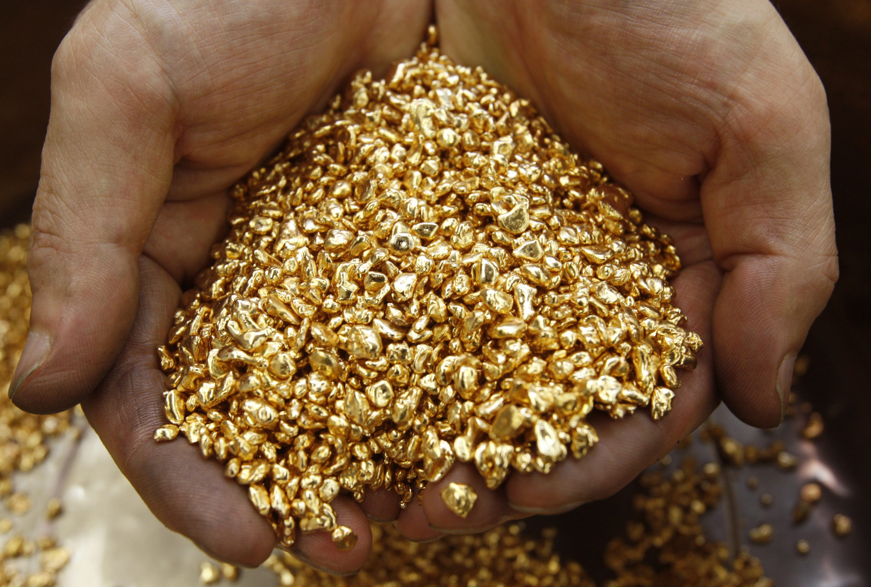 A worker scoops gold shots at a jewellery factory in Chiba, east of Tokyo